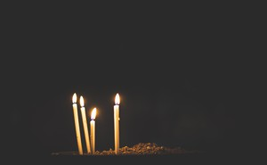 Four candles burn against a dark backdrop.