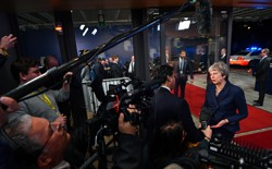Theresa May addresses reporters.