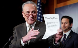 Chuck Schumer holds a printout from the Tampa Bay Times.