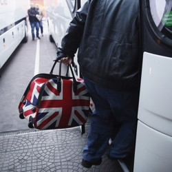 A man carries a bag with the British flag onto a bus.