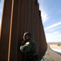 A U.S. Border Patrol Agent looks through the U.S.-Mexico border fencing in Santa Teresa, New Mexico