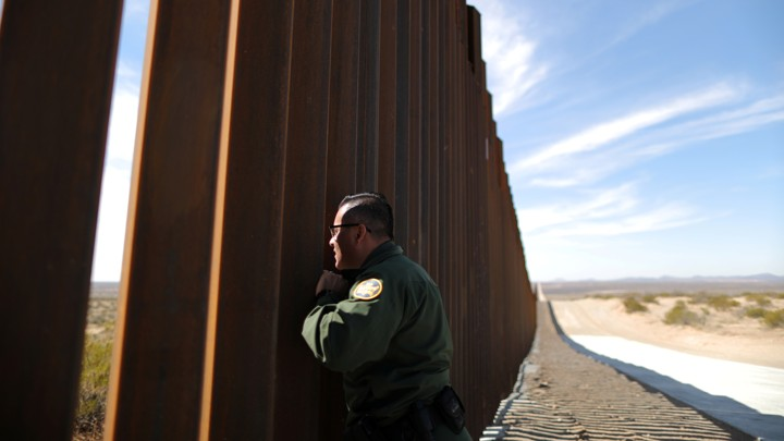 A U.S. Border Patrol agent looks through the U.S.-Mexico border fence in Santa Teresa, New Mexico.