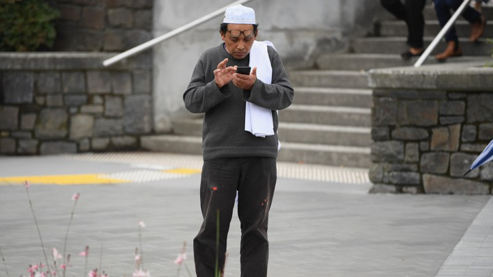 A survivor of the shooting at Al Noor mosque in Christchurch, New Zealand, waits for his wife to pick him up.