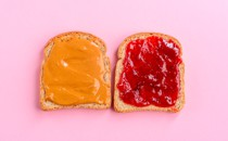 Two pieces of bread—one spread with peanut butter and one spread with jelly