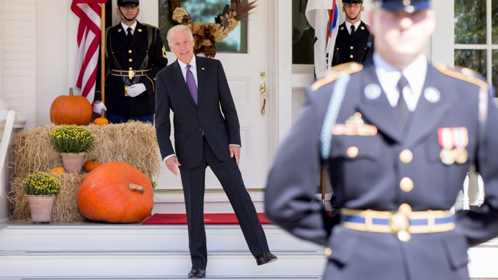 Joe Biden stands on one leg in front of the White House.