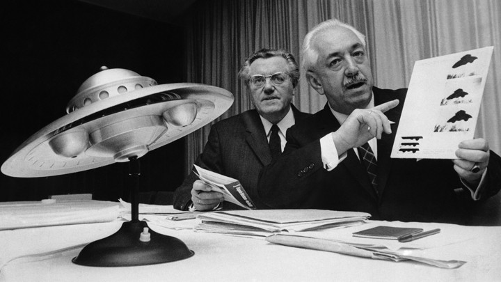 Officials speak at a news conference about UFOs in Germany in 1967, with a small replica of a flying saucer.