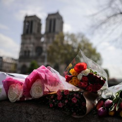 Flowers are laid on a bridge in front of the Notre-Dame cathedral a day after a fire devastated the building.