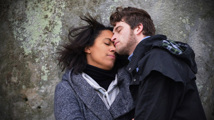 A man and a woman cuddle on a rock.