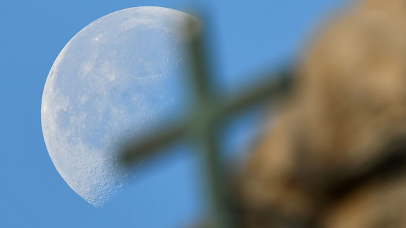 A large full moon sets behind a cross on St. Peter's Basilica in November 2016.