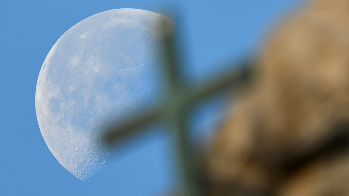 A large full moon sets behind a cross on Saint Peter's Basilica in November 2016.