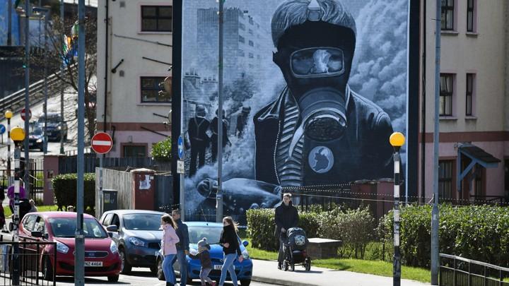 Pedestrians walk past a mural in Derry, Northern Ireland.
