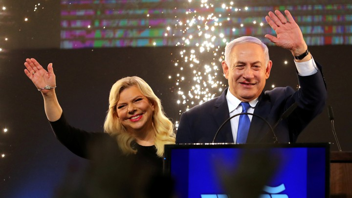 Benjamin Netanyahu and his wife, Sara, wave as Netanyahu speaks following the announcement of exit polling.