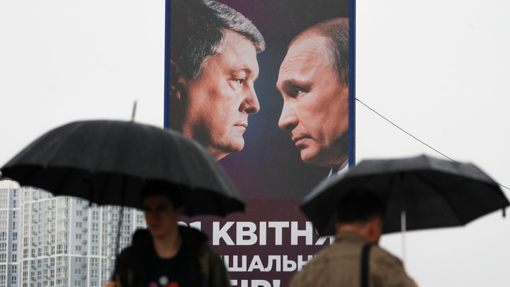 People walk past a campaign billboard, showing Poroshenko and Putin, in Kyiv.