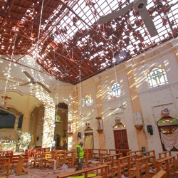 A crime-scene official inspects the site of a bomb blast inside a church in Negombo, Sri Lanka.