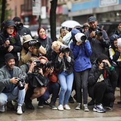 A crowd of paparazzi on the sidewalk