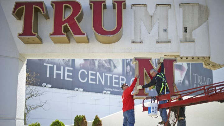 """A """"Trump"""" sign is taken down from a building"""