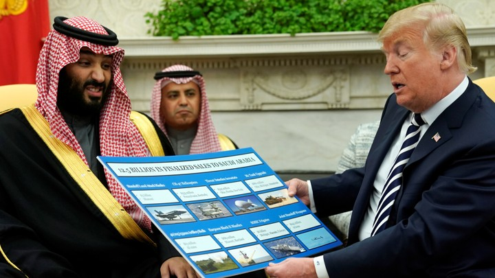 Donald Trump holds a chart of military hardware sales as he welcomes Saudi Arabia's Crown Prince Mohammed bin Salman in the Oval Office in May 2018