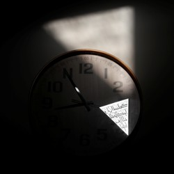 """A Koran verse that reads """"Allah is with those who are patient"""" is reflected on a clock at Al Noor mosque, where a white supremacist killed over 40 people in Christchurch, New Zealand. The attack was one in a recent wave of internet-inspired violence."""