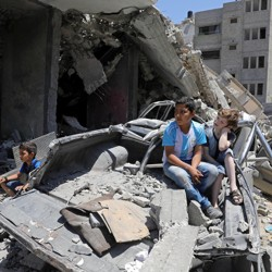 Palestinian children watch a band perform from the rubble of a building destroyed by Israeli air strikes