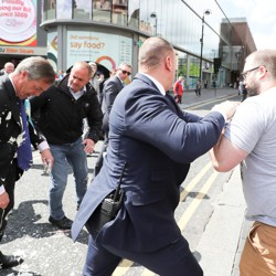 A security guard pushes back a man after he dumped a milkshake on Nigel Farage.