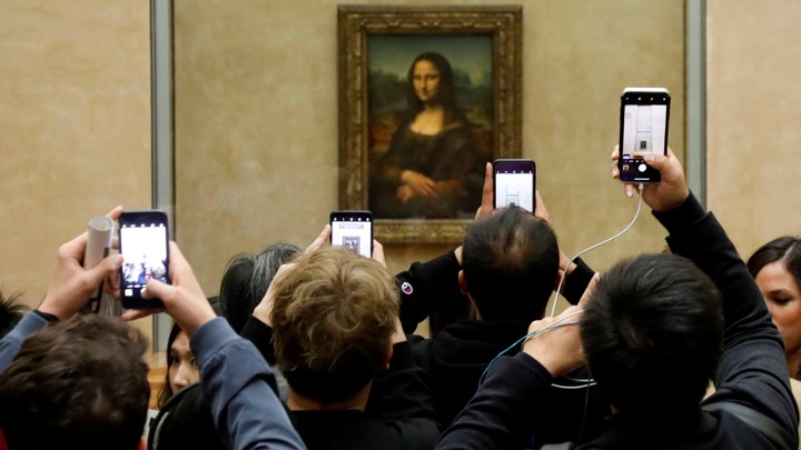 "A crowd of visitors taking pictures of the ""Mona Lisa"" painting at the Louvre"