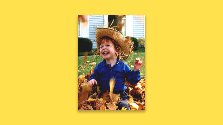 A young boy plays in a pile of leaves.