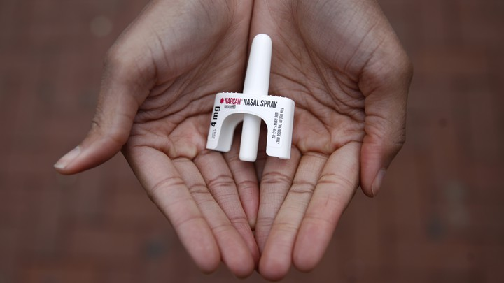 Hands holding a dose of Narcan nasal spray