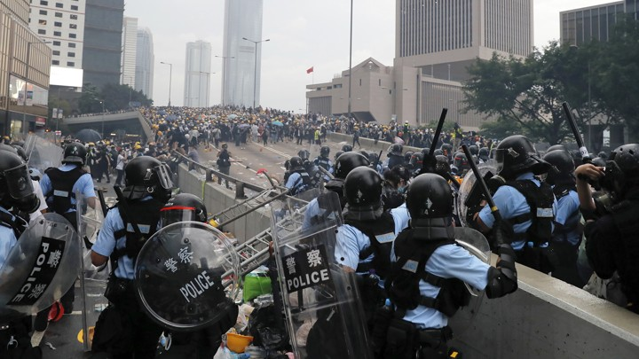 Riot police prepare to throw tear gas at protesters in Hong Kong.