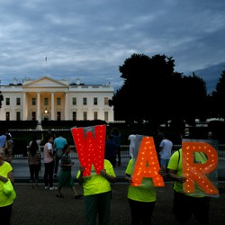 "Protesters hold signs that say ""No War"" outside the White House on June 20."
