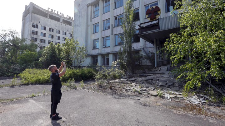 A man takes a photo of ruins in Pripyat, Ukraine.
