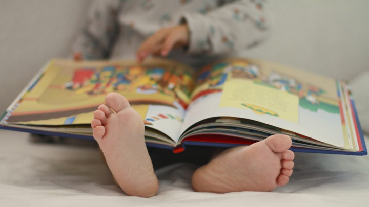 A small child reading a picture book on a bed