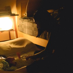 A woman puts a baby to bed in a crib.