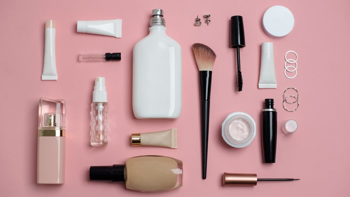 Numerous beauty products without labels arranged on a pink surface