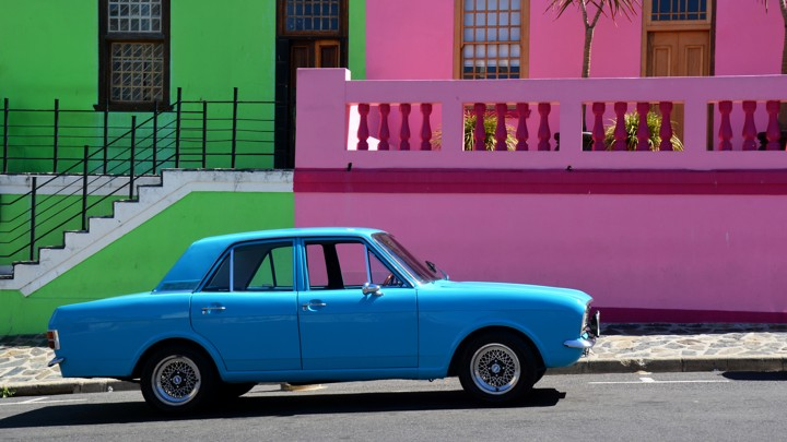 A bright blue car parked in front of pastel pink and green buildings