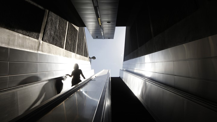A woman walks down the stairs to the entrance of a metro station.