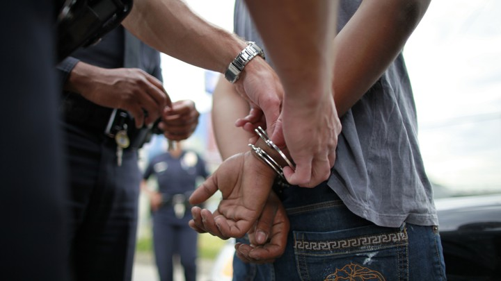 A police officer handcuffs a young man.