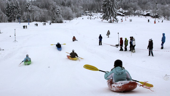 People compete during a snow-kayak downhill race near Otepää, Estonia, in 2013.