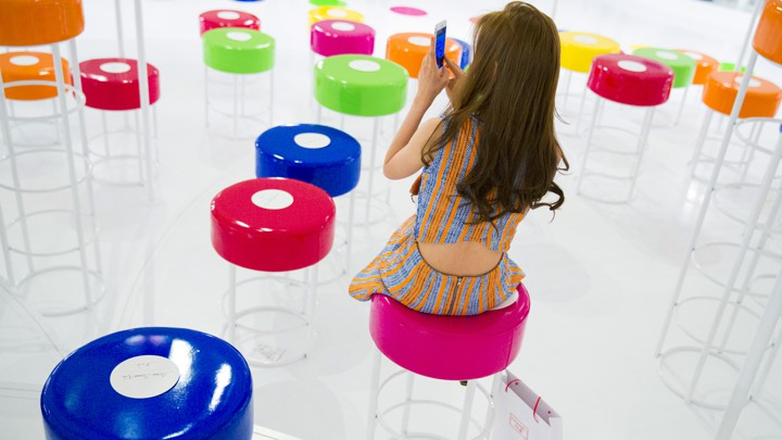 A woman looks at her phone while sitting among colorful stools.