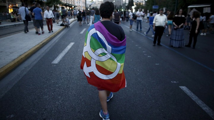 A gay-rights activist wearing a rainbow flag walks through the city center during a Gay Pride parade.