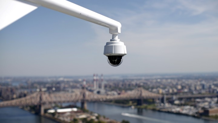 A security camera hangs from the roof of the Secretariat Building at the United Nations headquarters with the East River and Queensboro Bridge in the background in New York City.