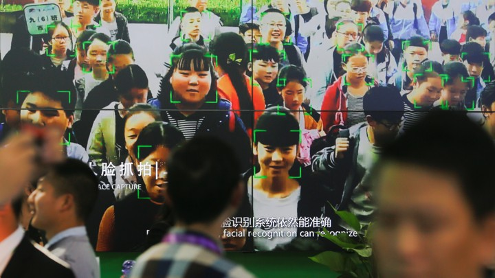 Visitors walk past a screen showing a demonstration of facial-recognition software at the Security China 2018 exhibition on public safety and security in Beijing.