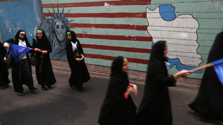 Iranian students walk past an anti-American mural, the Statue of Liberty with skull head and Iran's map.