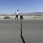 Two men examine a crack in highway 178 caused by the recent earthquakes in Ridgecrest, California.