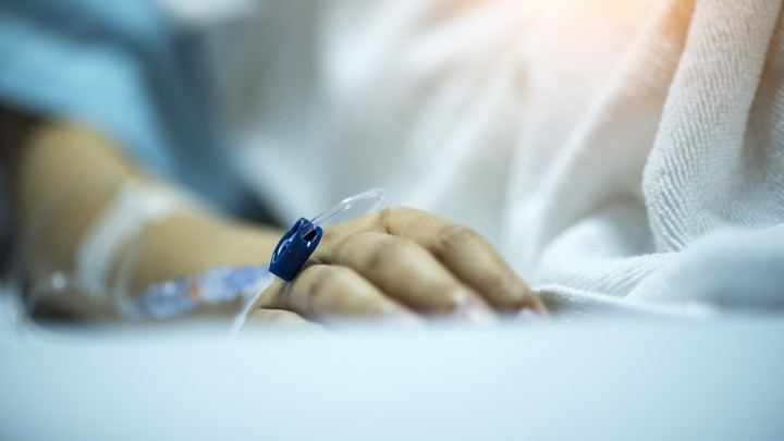 A hand rests on a hospital bed.