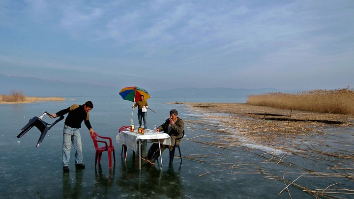 Three men set up a dining table in the middle of frozen water.