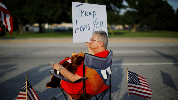 """Woman holds a sign that says """"Trump Loves You."""""""