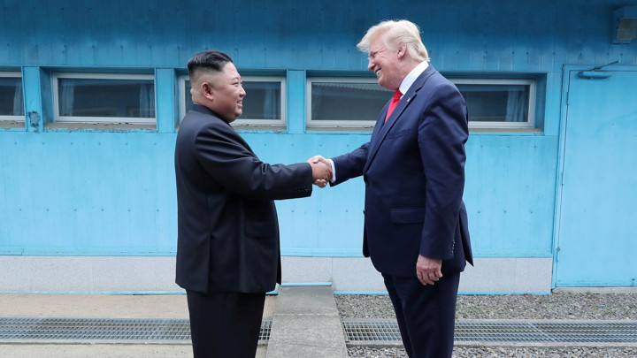 President Donald Trump shakes hands with Kim Jong Un.