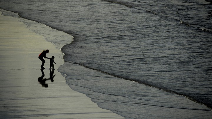 Silhouettes of a woman and a boy walking on a beach in Spain