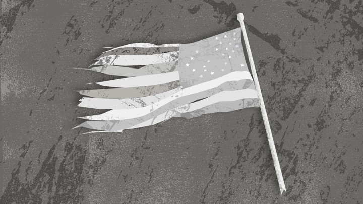 A tattered black-and-white American flag lying on the ground