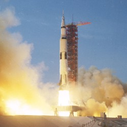 The Saturn V Rocket begins to launch, leaving behind it a trail of fire and clouds of smoke.